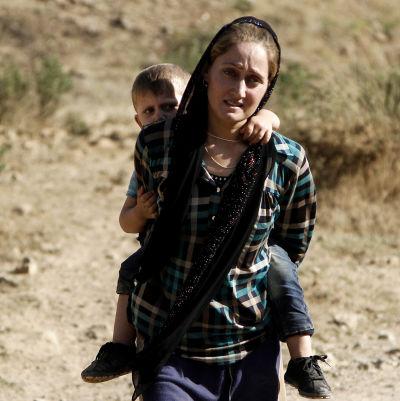 Yazidisk kvinna flyr undan IS med sin son på ryggen.