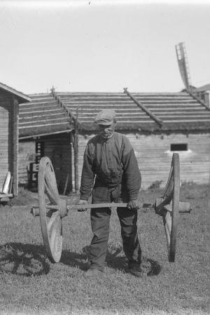 En man lyfter två kärrhjul. Bilden är tagen 1930 i Korsnäs.