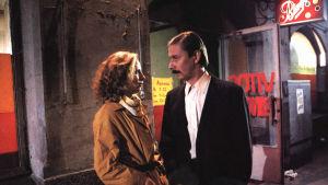 Kati Outinen ja Matti Pellonpää seisovat ulkona kadulla illalla ja katsovat toisiaan silmiin.