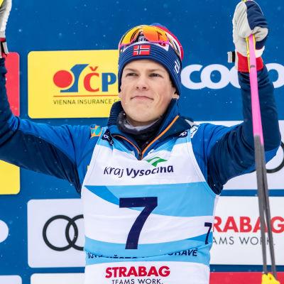 Johannes Hösflot Kläbo höjer nävarna i skyn på prispallen.