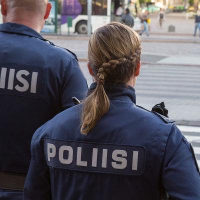 Två uniformklädda poliser står med ryggen mot kameran och blickar ut över Järnvägstorget i Helsingfors.