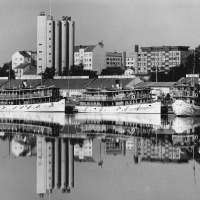 Kuva Mikkelin kaupungista satamasta päin 1960-luvulla. Etualalla varastomakasiinit ja taustalla kohoavat viljasiilot.
