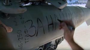 """Det ryska försvarsministeriets fotografi av en bomb där det står """"för vårt folk."""" Bilden är från en flygbas i Latakia som används av det ryska flygvapnet."""