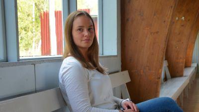 Ung kvinna sitter på bänk.