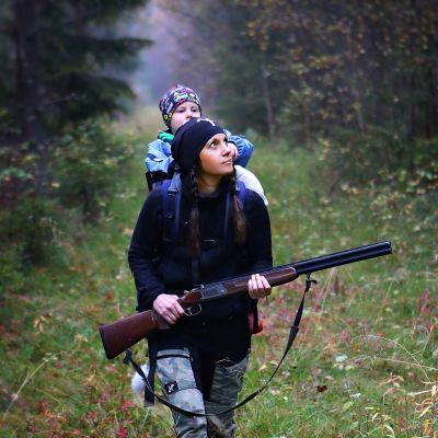 Marina går med ett av sina barn på ryggen och ett gevär i händerna.