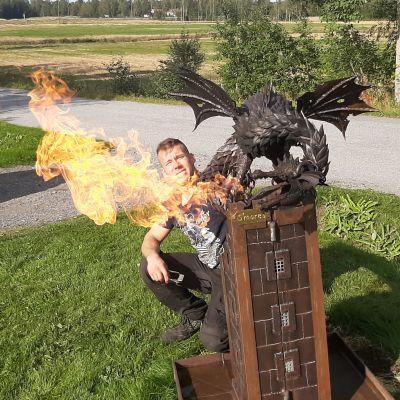 Drake i metall som sprutar eld.