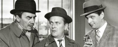 Svartvit bild från filmen Komisario Palmu. Tre män samtalar kring ett vitt papper.