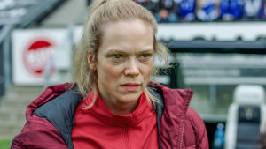 Helena i röd jacka och med bekymrad min.