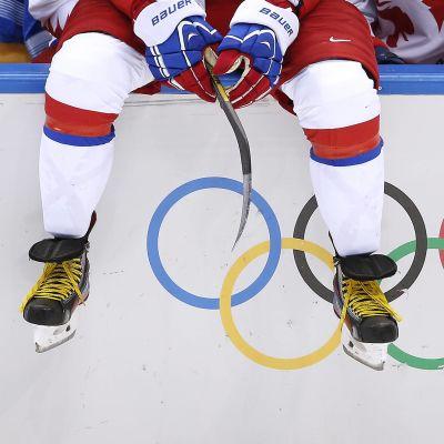 Ishockeyspelare sitter på sargen framför de olympiska ringarna.