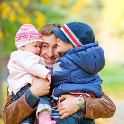En pappa med en pojke och en flicka i famnen.