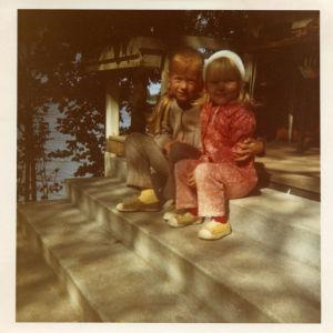 Kaksi lasta istuu kesämökin rappusilla.