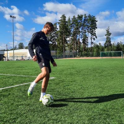 Ung man spelar fotboll på solig fotbollsplan.