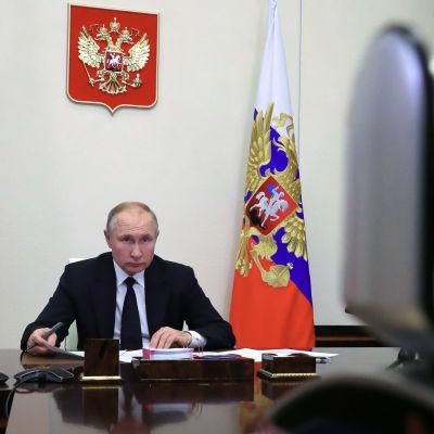 Vladimir Putin sitter vid ett mörkt och blankt skrivbord och tittar in i en videokamera.