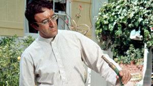 Peter Sellers intialaismiehen rooliasussa puutarhaletku kädessä. Kuva elokuvasta The Party eli Pahuksenmoiset pirskeet.