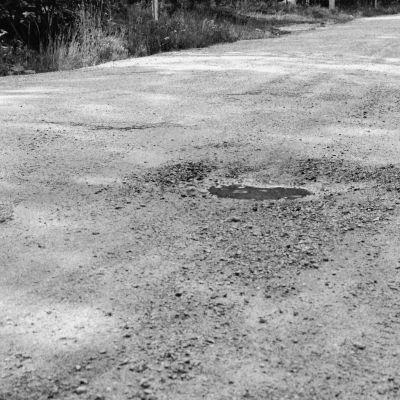 Svartvit bild av en grusväg, med en vattenpöl i  mitten, och skog på var sida om vägen.