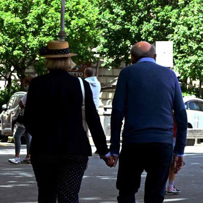 ett äldre par promenerar hand i hand i Rom