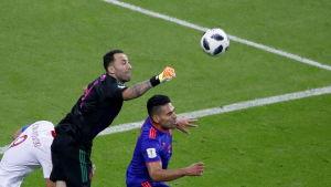 Målvakten David Ospina boxar undan en boll.