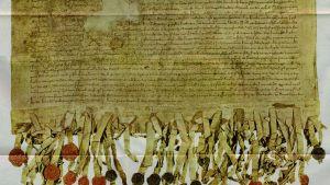 Ett gammalt dokument med text och sigiller i rött och svart. En kopia av Arbroathdeklarationen som utropade Skottland självständigt år 1320. Hade mest symboliskt värde.