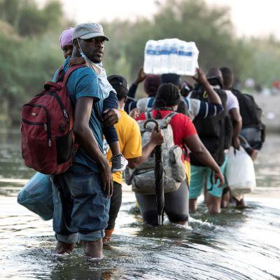Människor går i vattnet i en flod mellan Mexiko och USA. En person håller ett paket med stora vattenflaskor på huvudet.