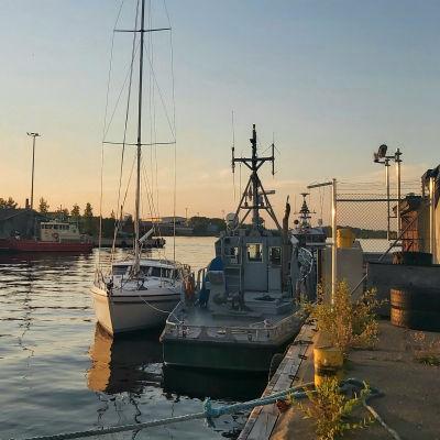 Kuva merivartioaseman veneestä, jonka vieressä kelluu valkoinen huvipursi.