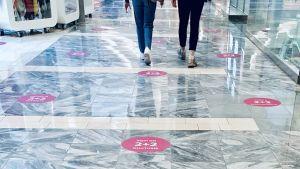 På golvet i ett köpcentrum i Tallinn påminner markeringar hur stort avstånd två meters social distansering är.
