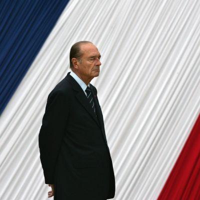 Jacues Chirac framför en stor fransk flagga.