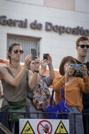 Turister med kameror fotograferar en spårvagn i Lissabon.