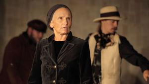 En kvinna klädd i svart i förgrunden och två män i bakgrunden. Kvinnan bär huvudduk och männen hatt.