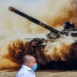 En man med ansiktsskydd framför en storbild på en rysk pansarvagn.