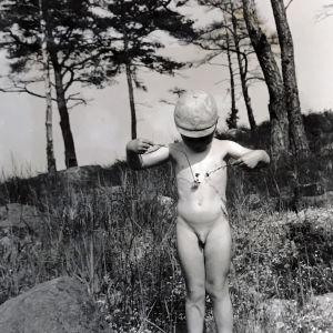 Pieni alaston poika kutittelee rintakehäänsä kukkasilla.