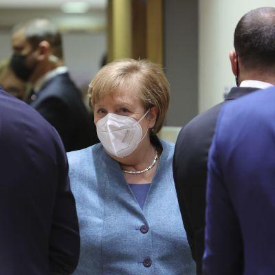 Saksan liittokansleri Angela Merkel kasvomaskiin sonnustautuneena.