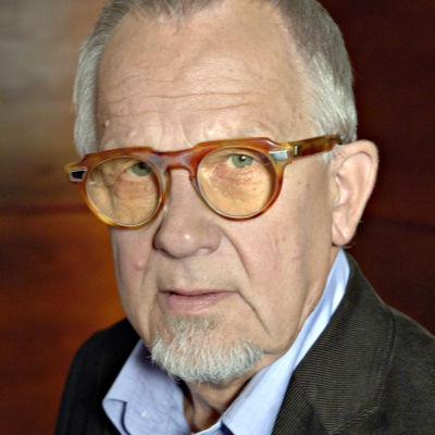 Kalle Holmberg katsoo kameraan, päässään oranssit silmälasit