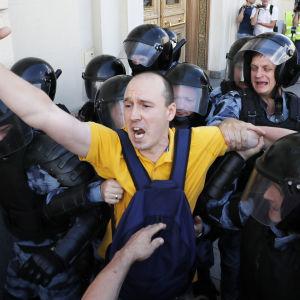 Demonstrant grips av poliser i Moskva.