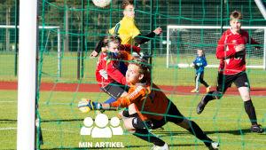 En målvakt försöker kasta sig efter en fotboll som går in i målet.