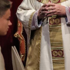 Romersk-katolsk präst och en pojke i en kyrka.