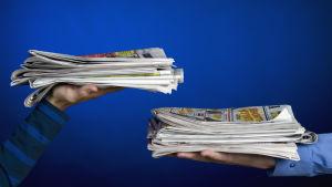 Sanomalehtiä pinoissa