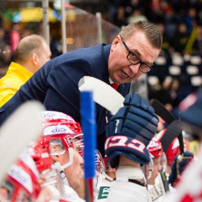 Ari-Pekka Selin står nerböjd och pratar med en spelare i båset