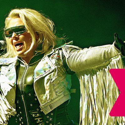 Kim Wilde bär solglasögon och sjunger i en mikrofon.