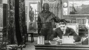 Fantômas seisoo kirjoituspöydän ääressä istuvan miehen takana. Kuva elokuvasarjasta Fantômas