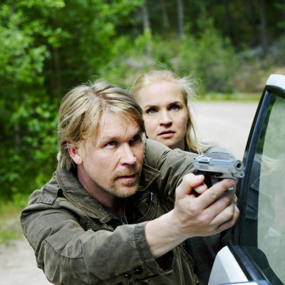 Mies ja nainen kyyryssä auton oven vieressä. Mies osoittaa aseella pois kuvasta, nainen hänen takanaan. Sarjasta Pirunpelto.