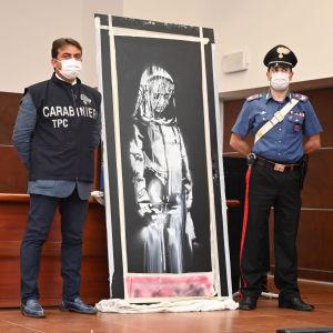 Kaksi poliisia esittelee Banksyn teosta.