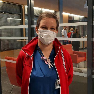 Sairaanhoitaja Carita Kangas työvaatteissaan sairaalan aulatiloissa