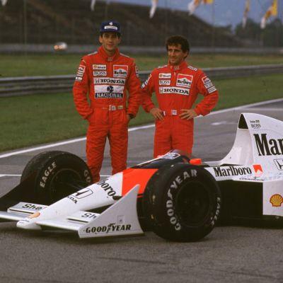 Ayrton Senna ja Alain Prost poseeraavat F1-auton vieressä.