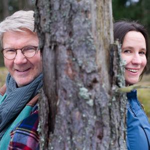 Pirkka-Pekka Petelius ja Minna Pyykkö nojaavat mäntyyn.