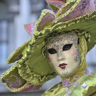 Vihreän ja roosan sävyiseen naamiaisasuun ja päähineeseen sekä taidokkaasti koristeltuun naamioon pukeutunut henkilö Venetsian karnevaaleissa.