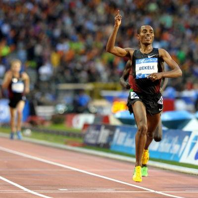 Etiopisk distanslöpare löper i mål och höjer handen i en segergest.