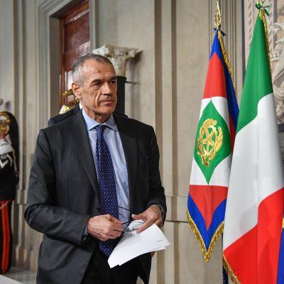 Carlo Cottarelli vid den italienska och EU-flaggan.