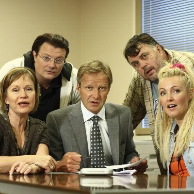 Ihmisten puolue -sarjan hahmot pöydän ääressä.