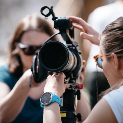 Två kvinnor justerar en kamera.