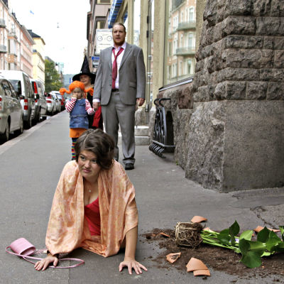 Joanna Haartti kompastuneena kadulla rikkinäinen kukkaruukku vierellään, Santtu Karvonen ja lapset seisovat taustalla. Kuva lyhytelokuvasta Pitääkö mun kaikki hoitaa?.